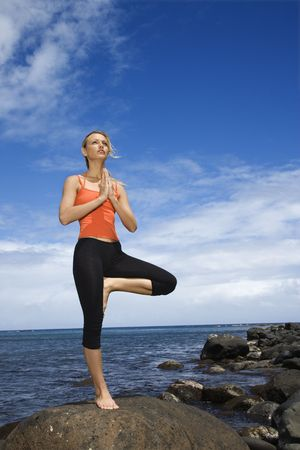 Caucasian young adult woman doing yoga on rocky shore. Stock Photo - 1798914