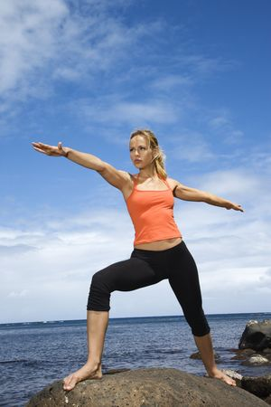 Caucasian young adult woman doing yoga on rocky shore. photo