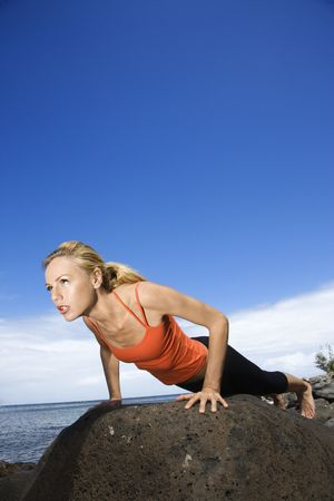 Caucasian young adult woman doing push up on rock. photo
