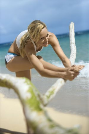 Caucasian young adult woman stretching on beach. Stock Photo - 1798878