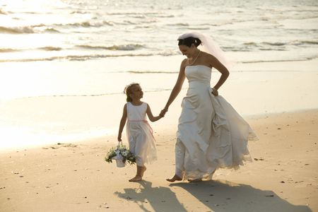 Caucasian mid-adult bride and flower girl holding hands walking barefoot on beach. photo