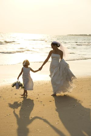 Caucasian mid-adult bride and flower girl holding hands walking barefoot on beach. Stock Photo - 1795806