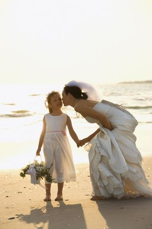 Caucasian mid-adult bride kneeling to give flower girl a kiss on the cheek while holding hands barefoot on beach. photo