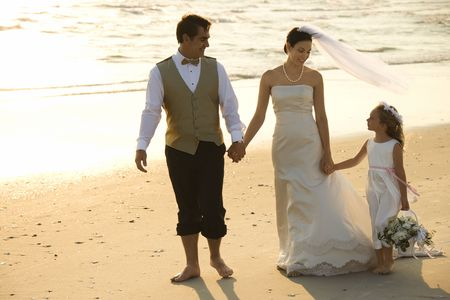 beach wedding: Caucasian mid-adult bride, mid-adult groom and flower girl holding hands walking barefoot on beach.