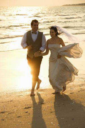 Caucasian mid-adult bride and mid-adult groom holding hands running barefoot on beach. Stock Photo - 1796043