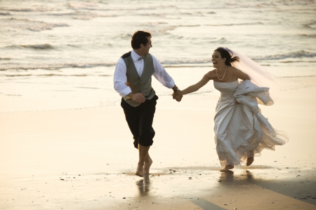 Caucasian prime adult male groom and female bride running barefoot on beach.