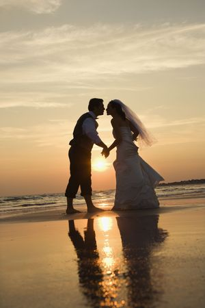 beach wedding: Caucasian prime adult male groom and female bride holding hands and kissing barefoot on beach at sunset. Stock Photo