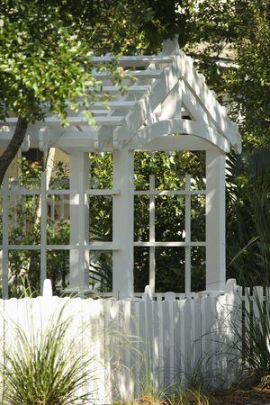 entrance arbor: Garden arbor with white picket fence. Stock Photo