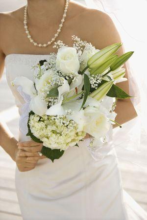 Caucasian mid-adult bride holding flower bouquet. Stock Photo - 1795525