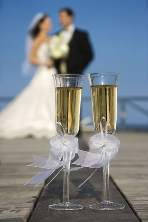 Pair of flute glasses of champagne with Caucasian bride and groom blurred in background. photo