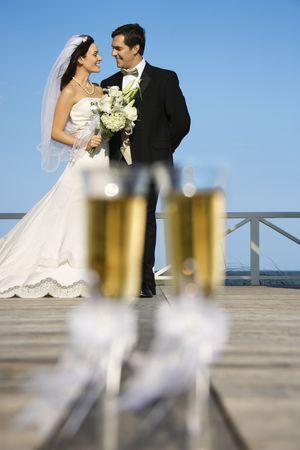 El par de cristales de la flauta de champán con la novia caucásica y prepara en fondo.
