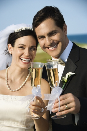 Caucasian mid-adult bride and groom toasting champagne looking at viewer and smiling. photo