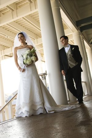 Caucasian mid-adult fbride and groom standing on porch. Stock Photo - 1795813