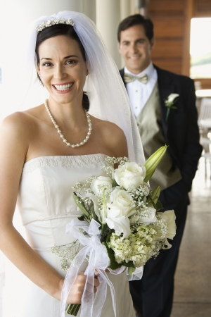 Caucasian mid-adult bride and groom standing on porch looking at viewer and smiling.