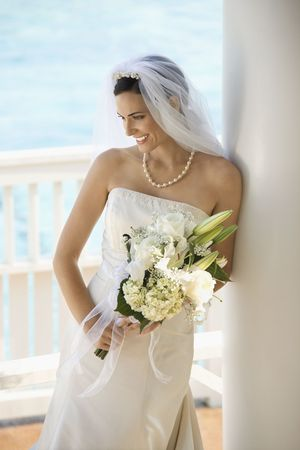 Caucasian mid-adult bride holding bouquet looking down. photo