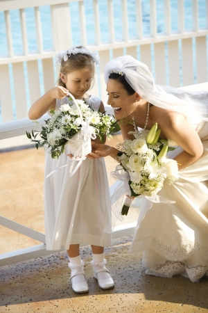 Caucasian mid-adult bride kneeling next to flower girl admiring her flowers. Stock Photo - 1795812