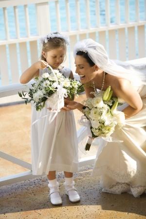 Caucasian mid-adult bride kneeling next to flower girl admiring her flowers. photo