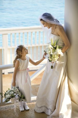 Caucasian mid-adult bride holding hands with flower girl. Stock Photo - 1795800