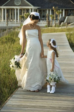 Caucasian mid-adult bride holding hands with flower girl walking down wooden beach walkway. photo