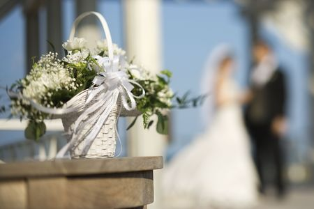 Flower basket with Caucasian bride and groom blurred in background. Stock Photo - 1795515