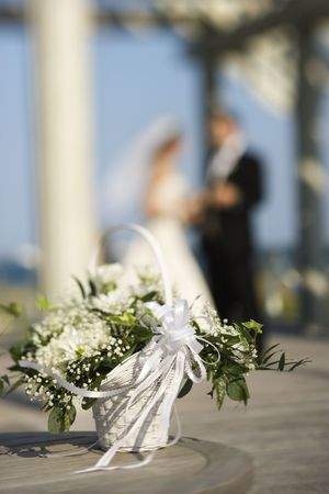 flower basket: Flower basket with Caucasian bride and groom blurred in background.