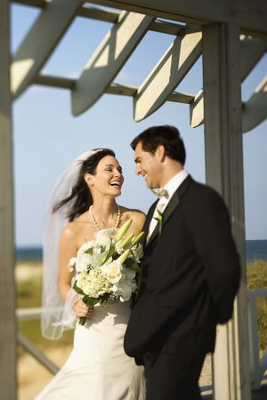 love image: Caucasian mid-adult bride and groom looking at each other talking and laughing.