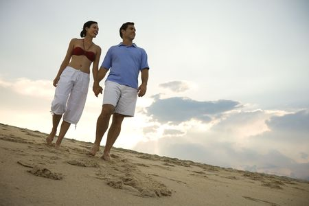 Caucasian mid-adult couple holding hands walking on beach. Stock Photo - 1796908