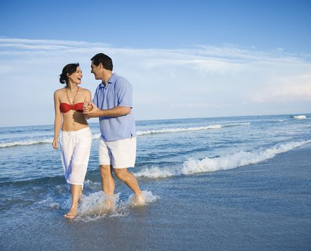 Caucasian mid-adult couple holding hands wading in ocean.