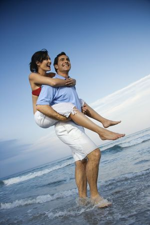 bald head island: Caucasian mid-adult male carrying female piggyback style on beach. Stock Photo