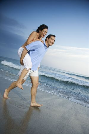 Caucasian mid-adult male carrying female piggyback style on beach. photo