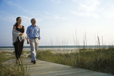 and the horizontal man: Caucasian mid-adult couple holding hands and walking down walkway at beach.
