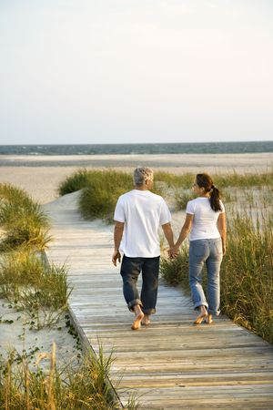 Back view of mid-adult Caucasian couple walking down walkway to beach. Stock Photo