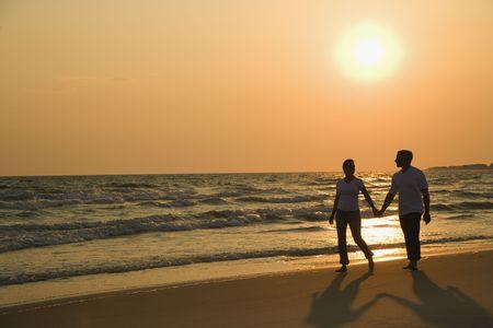 parejas caminando: Pares cauc�sicos del mediados de-adulto que llevan a cabo las manos y que caminan abajo de la playa en la puesta del sol.
