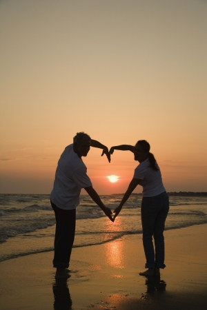 couple holding hands: Mid-adult couple making heart shape with arms on beach at sunset.
