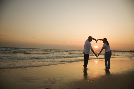 husbands: Mid-adult couple making heart shape with arms on beach at sunset.