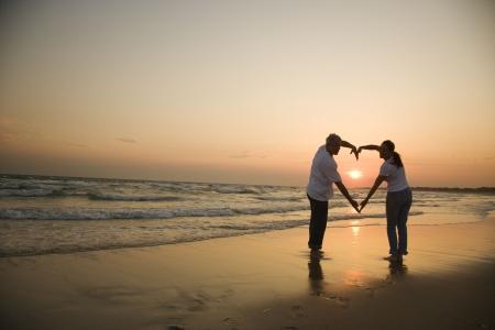 Ehefrauen: Mid-erwachsene Paar macht Herzen Form mit Waffen am Strand bei Sonnenuntergang.  Lizenzfreie Bilder