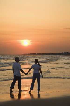 Mid-adult couple holding hands and walking on beach at sunset. photo