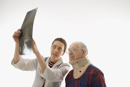 Mid-adult Caucasian female doctor showing x-ray to elderly Caucasian male in neck brace. Stock Photo