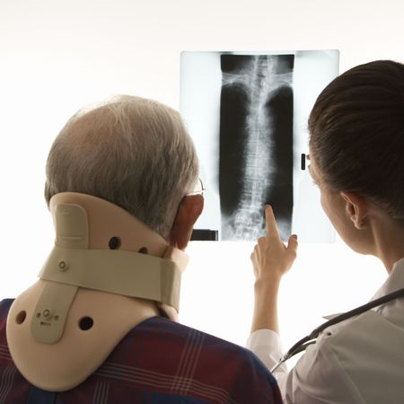 neck brace: Over the shoulders view of mid-adult Caucasian female pointing at an x-ray as elderly Caucasian male in neck brace looks on. Stock Photo