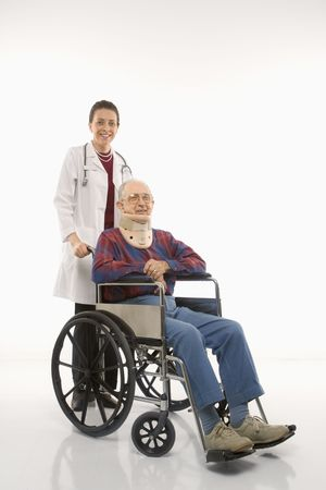 Mid-adult Caucasian female doctor pushing elderly Caucasian male with neck brace in wheelchair. Stock Photo