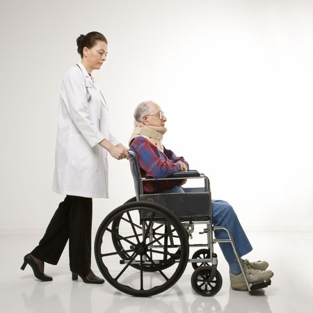 neck brace: Mid-adult Caucasian female doctor pushing elderly Caucasian male with neck brace in wheelchair. Stock Photo