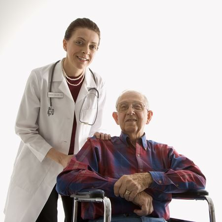 Mid-adult Caucasian female doctor with hands on elderly Caucasian males shoulder in wheelchair.