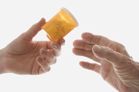 Close-up of mid-adult Caucasian female's hand handing medication bottle to elderly Caucasian male hand. Stock Photo - 1797076