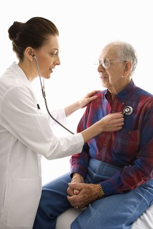 Mid-adult Caucasian female doctor listening  to elderly Caucasian males heart with stethoscope. photo