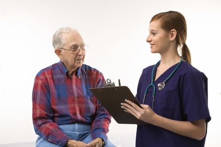 Mid-adult Caucasian female in scrubs taking notes from elderly Caucasian male. photo