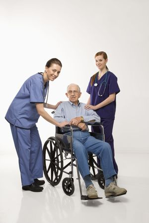 Two Caucasian females wearing scrubs with elderly Caucasian male in wheelchair. Stock Photo - 1795510