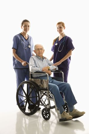 Two Caucasian females wearing scrubs with elderly Caucasian male in wheelchair. photo