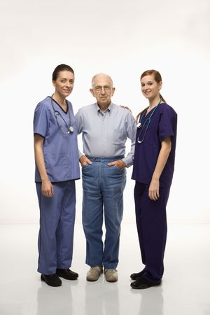 Two Caucasian females wearing scrubs standing with elderly Caucasian male. Stock Photo