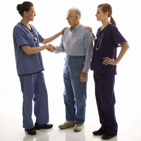 Mid-adult Caucasian female in scrubs shaking hand of elderly Caucasian male with another mid-adult Caucasian female with hand on his shoulder. photo