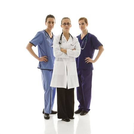 Full-length portrait of Caucasian women healthcare workers in uniforms standing against white background. photo